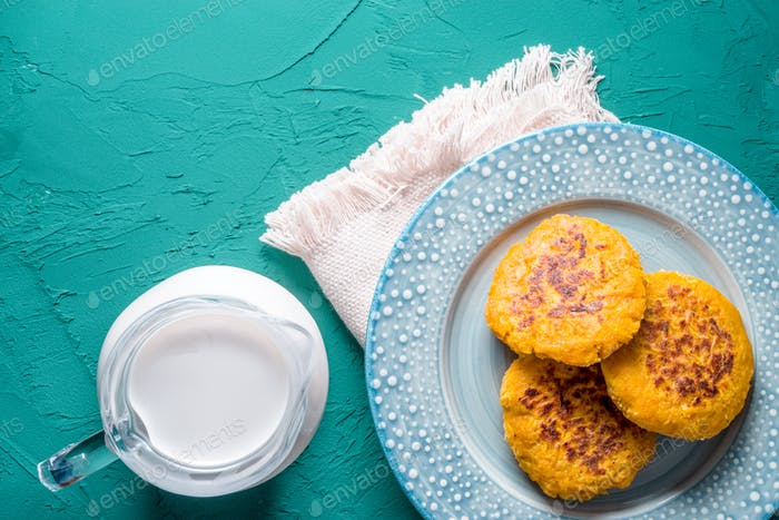 Hemp milk and pumpkin pancakes on a turquoise background