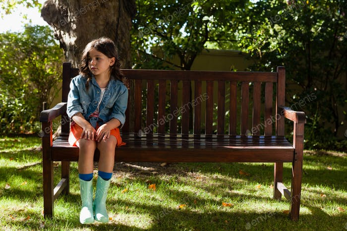 Girl wearing casual sitting on wooden bench