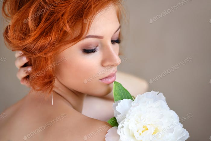 Portrait of young beautiful redhaired woman with white flower. Beauty portrait