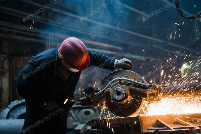 Employee grinding steel with sparks - focus on grinder. Steel factory
