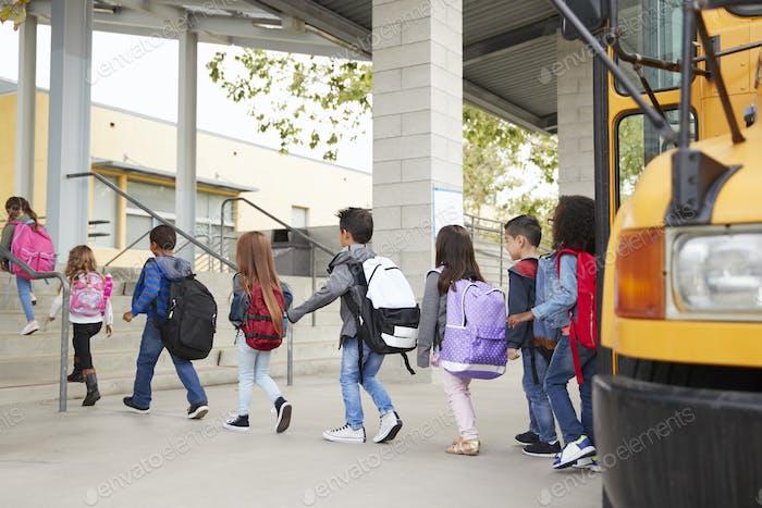 Los Niños de la escuela primaria llegan a la escuela desde el autobús escolar