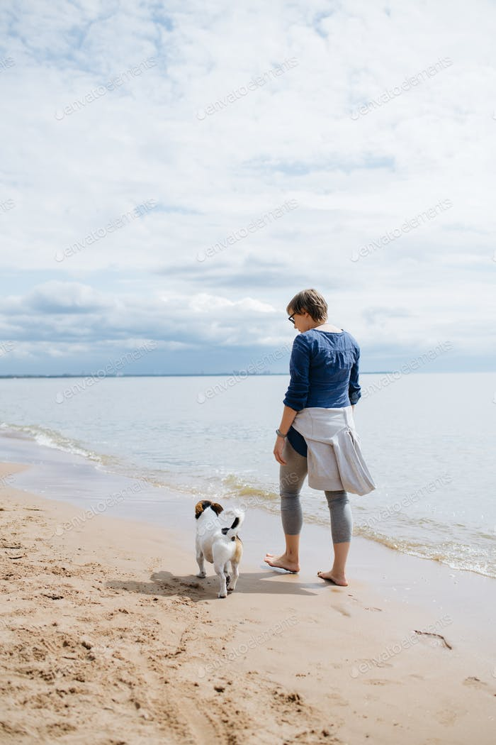 Woman walking with her dog on the sandy beach. Rear view.
