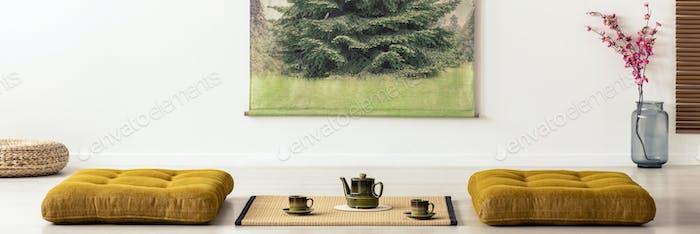 Wasserkocher und Tassen auf Tatami-Matte zwischen Kissen im Esszimmer in
