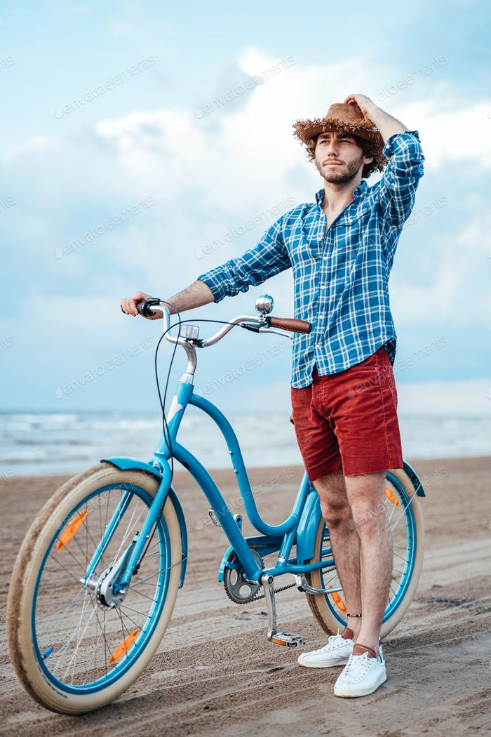 Attentive boy with a straw hat is walking on the beach with his blue bike