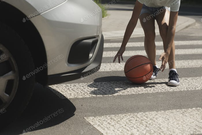 Close-up on kid with ball on pedestrian crossing next to car