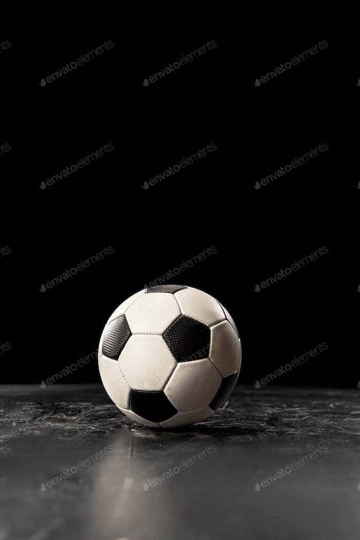 Einzelfußball auf schwarzem Boden