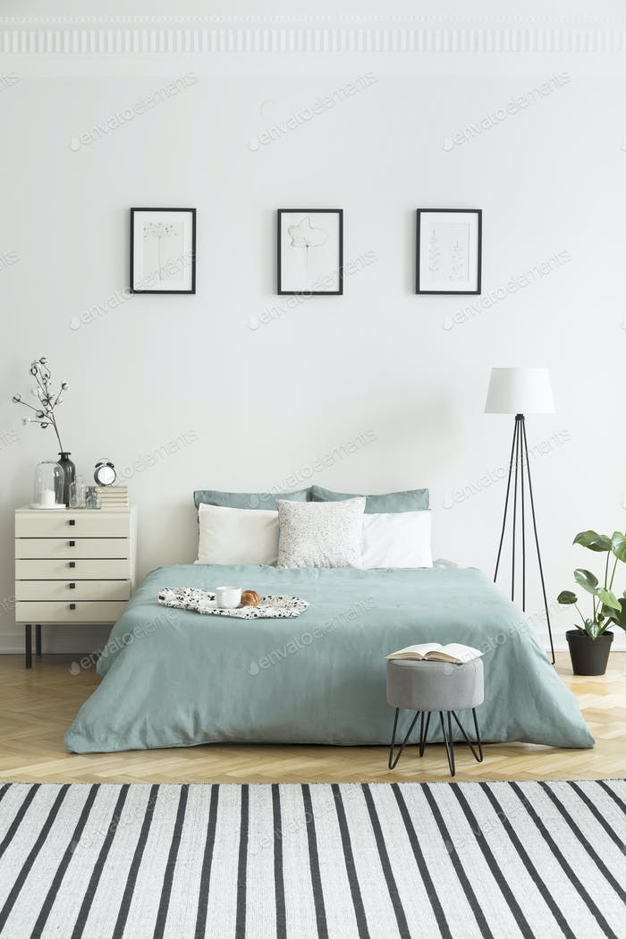Posters on white wall above green bed in bedroom interior with s