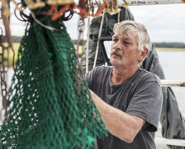 Commercial fisherman mending net.