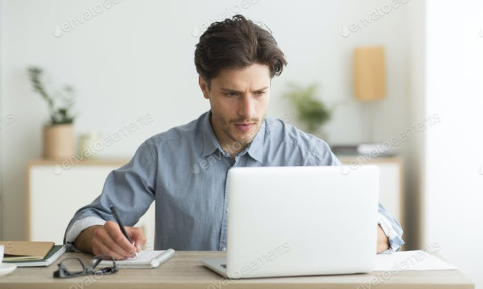 Young Entrepreneur Working On Laptop And Taking Notes Indoor