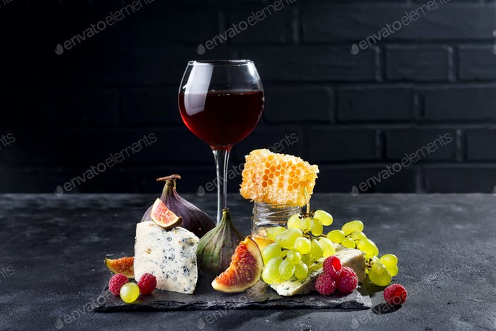 Grape, cheese, figs and honey with a glasses of red on a stone black background, copy space