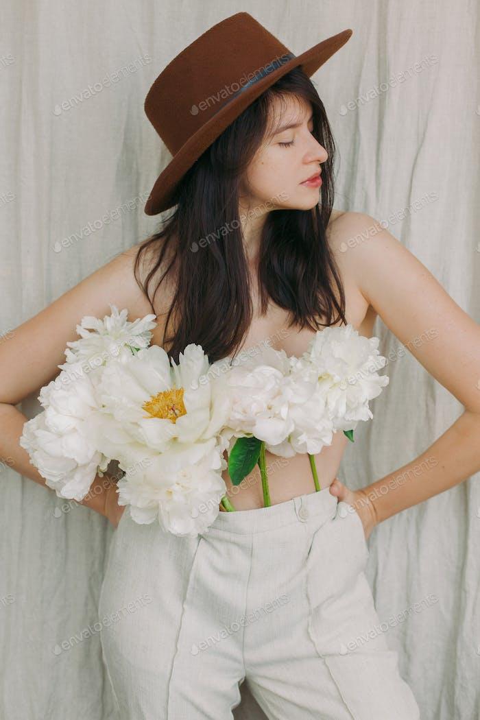 Imagen sensual de hermosa mujer con ramo de peonía en lugar de camisa