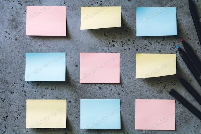 Bunte, leere Haftnotizen auf grauem Hintergrund. Die Konzeption Organisation und Planung.