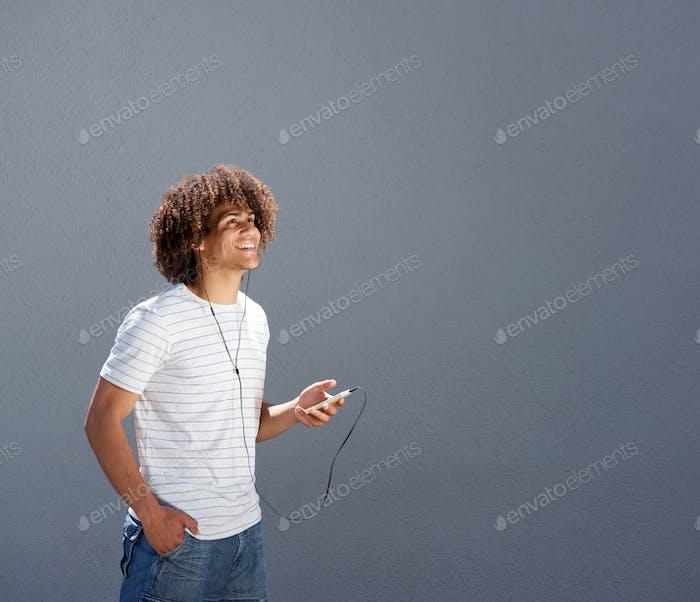 Mann zu Fuß draußen und Musik hören mit Smartphone