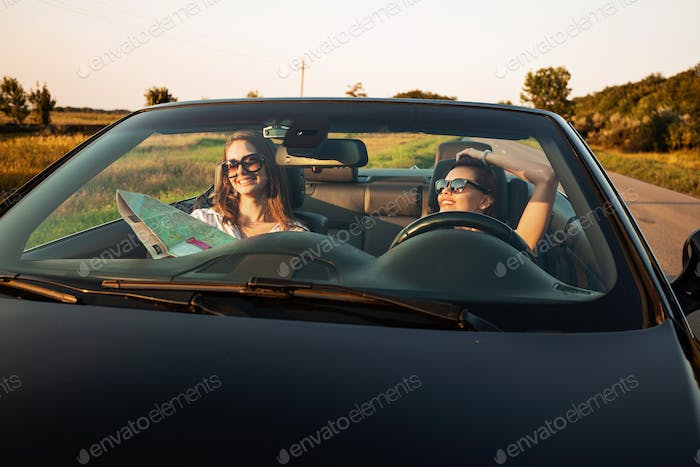 Beautiful dark-haired young women in sunglasses are sitting in a black cabriolet on a sunny day. One