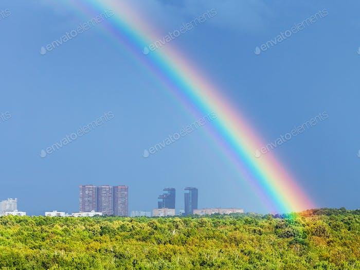 rainbow in blue rainy sky over city and urban park
