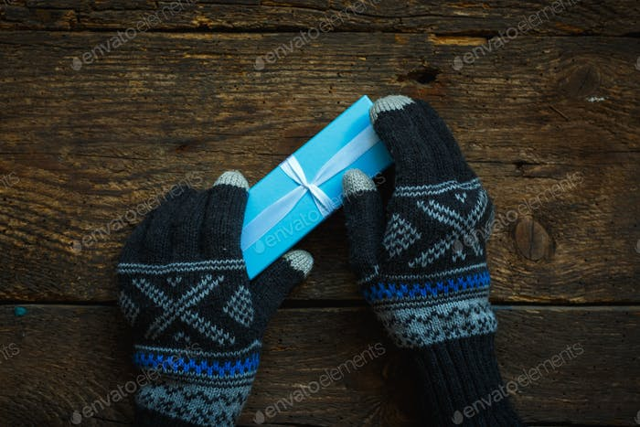 Hands in winter gloves with christmas gift box