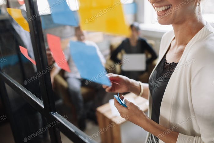 Smiling woman brainstorming using adhesive notes