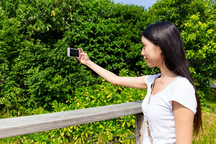 Woman take photo at green park