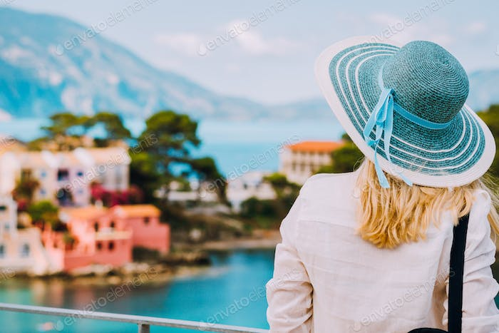 Tourist woman wear blue sunhat and white clothes admire view of colorful tranquil village Assos on