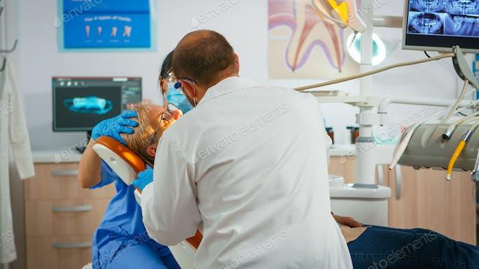 Senior woman sitting on dentist chair at dental clinic