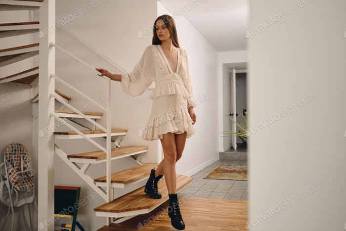 Beautiful girl in white dress and black boots going down stairs dreamily looking aside at home