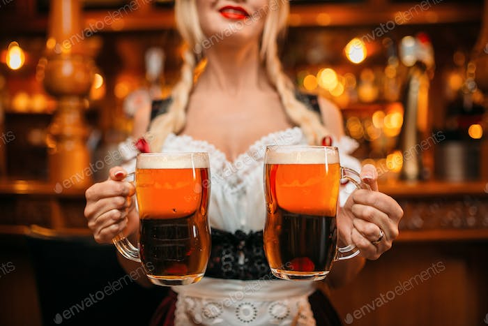 Sexy waitress holds two mugs of fresh beer in pub