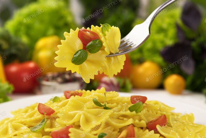 Plate of italian pasta, farfalle on fork with tomatoes and basil