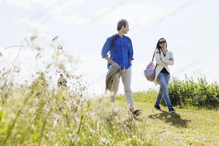 Friends walking on grassy field against clear sky