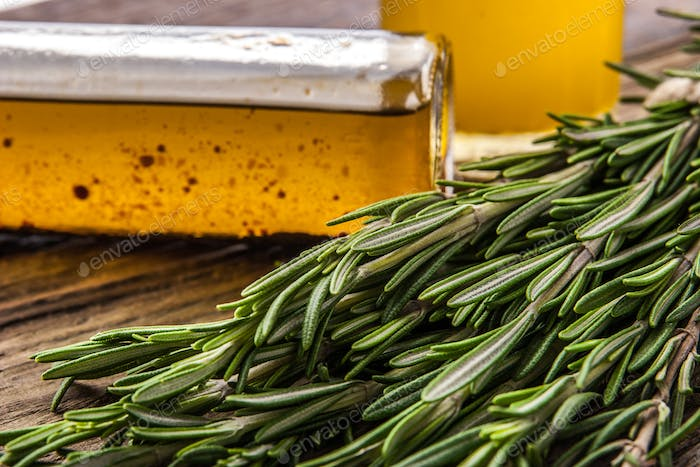 Bunch of rosemary with blurred olive oil close-up