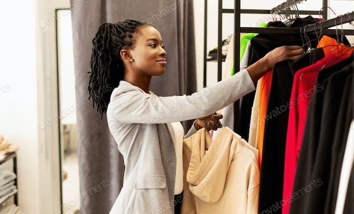 Señora Negro Recogiendo Ropa De Moda En Boutique De Moda