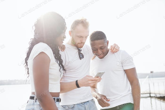 Group of multiracial happy friends using gadget outdoors