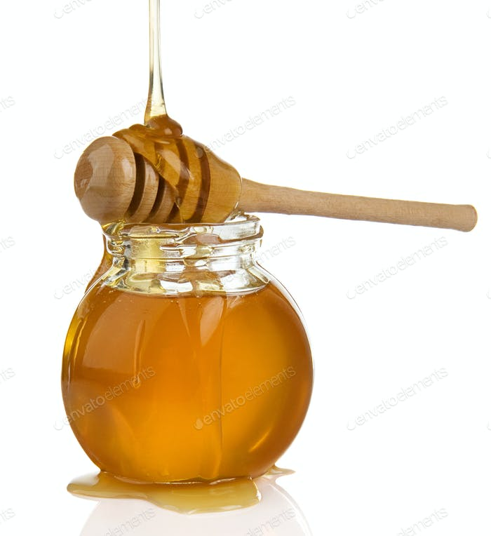 glass pot full of honey and stick on white