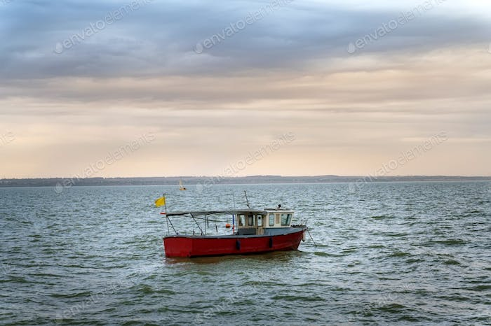 Photo of motor fishing boat under dark clouds with yellow flag