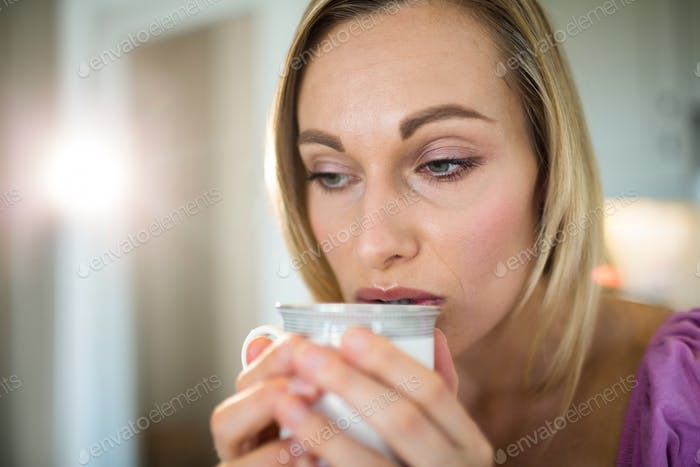 Pretty blonde woman having coffee at home