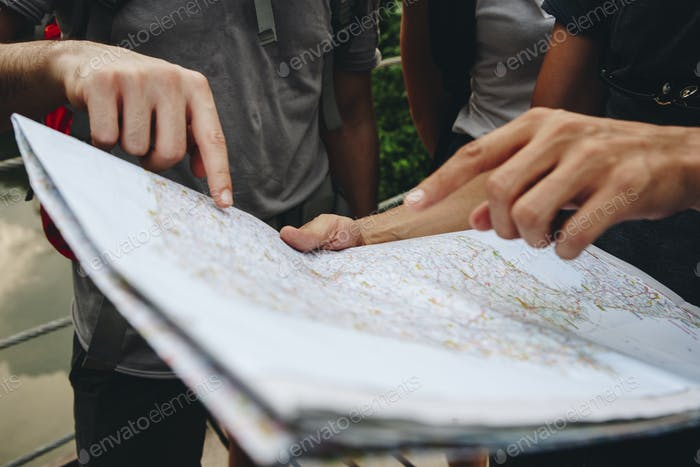 Group of friends looking at a map together travel and teamwork concept