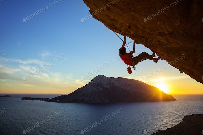 Young man climbing overhanging cliff at sunset