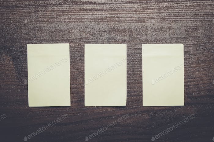 three blank stickers on brown wooden table