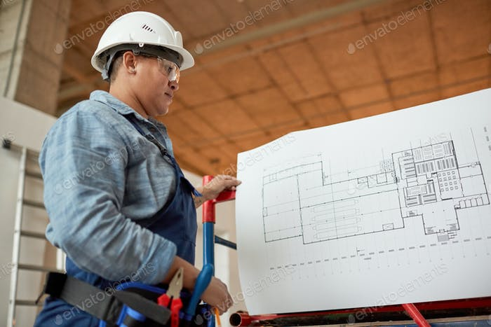 Female Worker Looking at Plans on Site