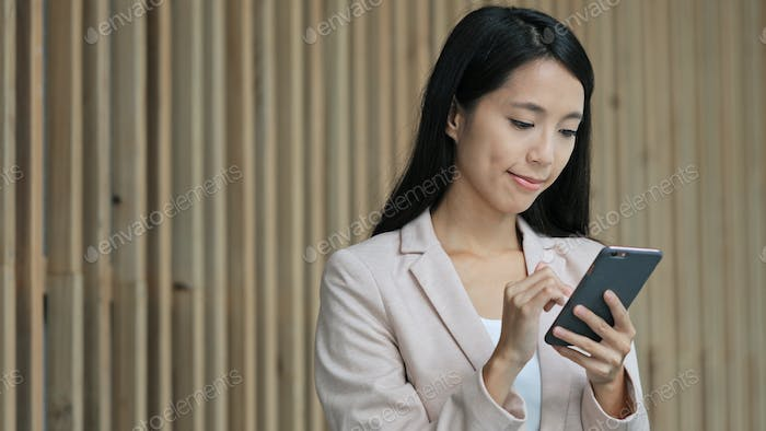 Business woman working on cellphone in corporate building