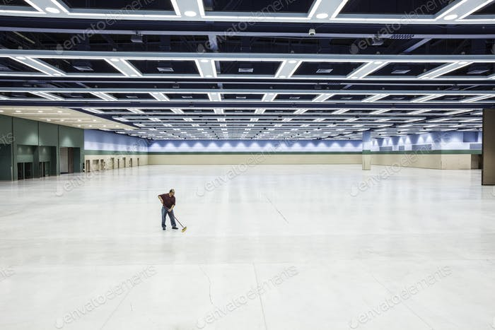 A lone man sweeping the floor of a convention center arena area.