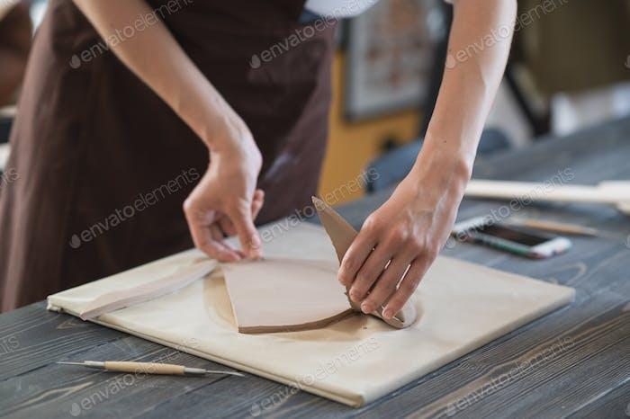 Frauenfinger Hinzufügen und Einstellen eines Tonteils auf ein zukünftiges Keramikprodukt
