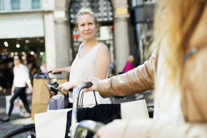 Shopaholic women with bicycles in city