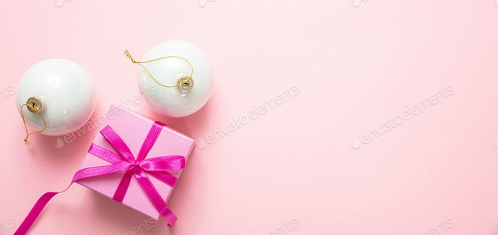 Xmas baubles and gift box against pink background, top view, copy space
