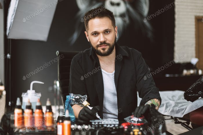 Smiling tattooer in black gloves dreamily looking in camera hold