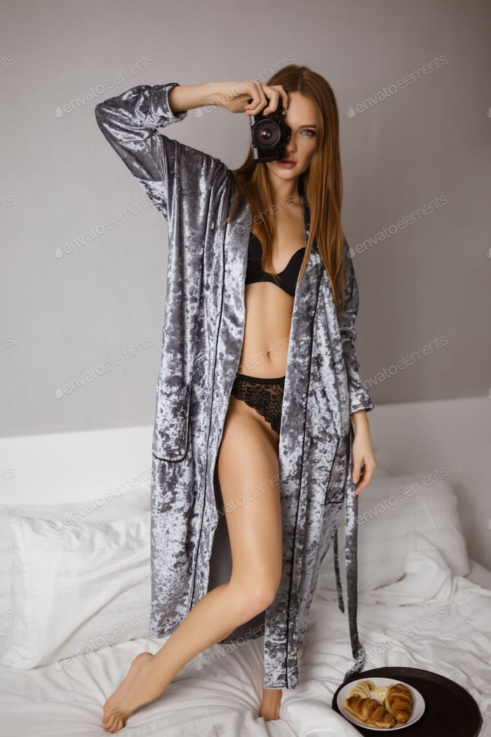 Beautiful lady in lingerie and velvet robe standing in bed and holding black little camera in hand