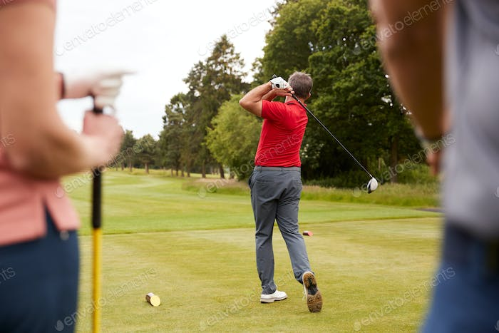 Golf Professional Demonstrating Tee Shot To Group Of Golfers During Lesson