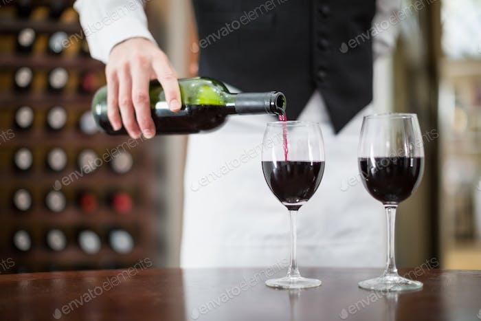 Männlicher Kellner gießt Wein in Weingläsern