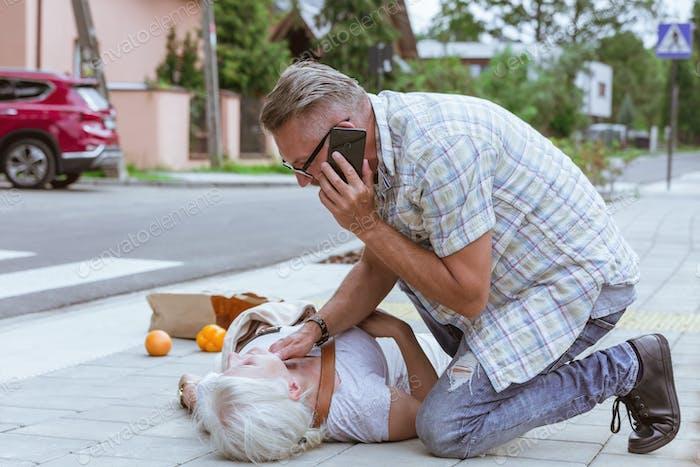 Senior Passant kniet neben der Person, die auf der Straße in Ohnmacht fiel und ruft einen Krankenwagen
