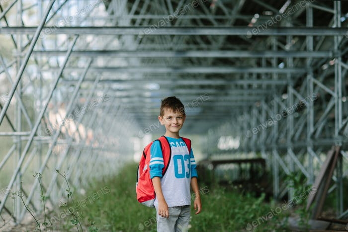 Portrait of a smiling child with a bag on his way to school