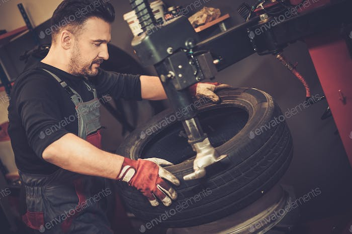 Professional car  mechanic replace tire on wheel in auto repair